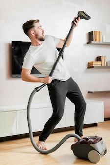 Mann tanzt mit staubsauger