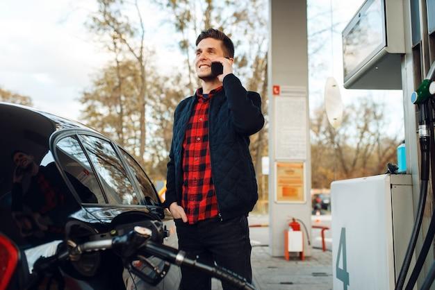 Mann telefoniert und betankt fahrzeug an tankstelle, tankfüllung. benzintanken, benzin- oder dieseltankservice