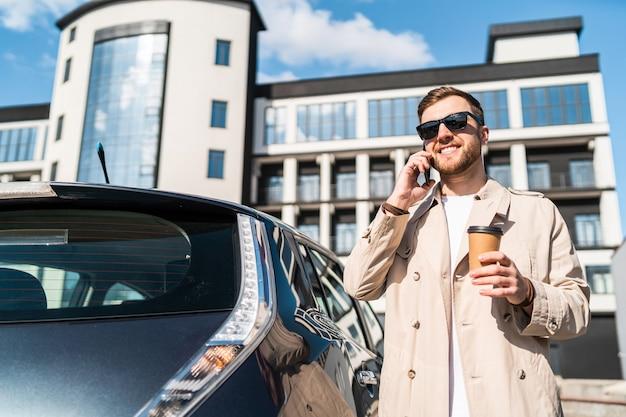 Mann telefoniert, während sein auto an der station lädt