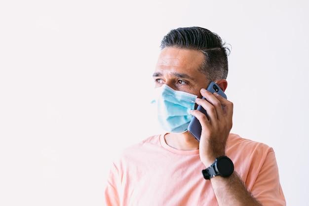 Mann teleworking von zu hause, der eine chirurgische maske trägt, um sich vor covid19 zu schützen