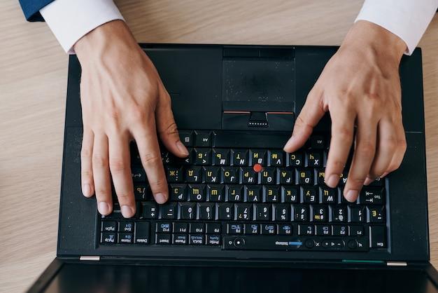Mann tippt auf draufsicht der laptop-tastatur