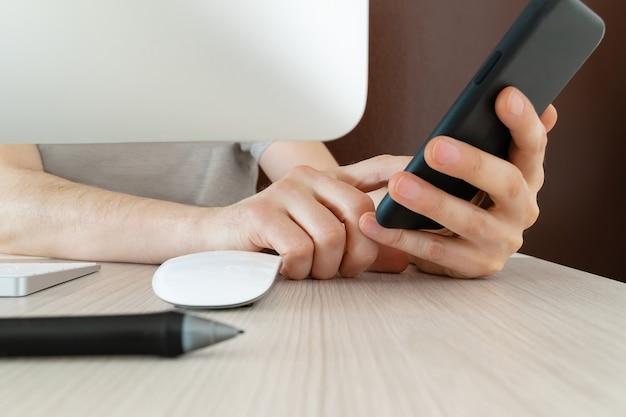 Mann tippt auf smartphone und arbeitet zu hause mit computer von hinten gesehen