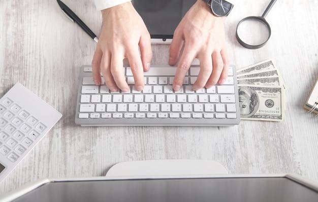 Mann tippt tastatur ein. dollar banknoten auf dem schreibtisch