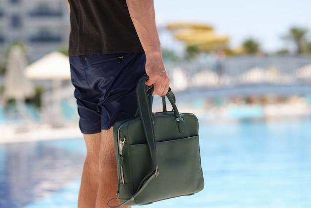 Mann tourist in shorts hält business-tasche im hintergrund des hotelpools