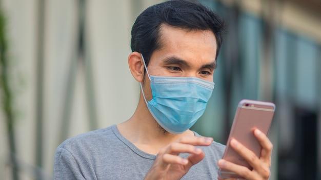 Mann trägt chirurgische maske, schützt covid19 und verwendet smartphone im freien