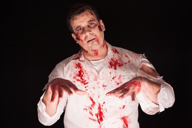 Mann trägt ein gruseliges kostüm für halloween auf schwarzem hintergrund.
