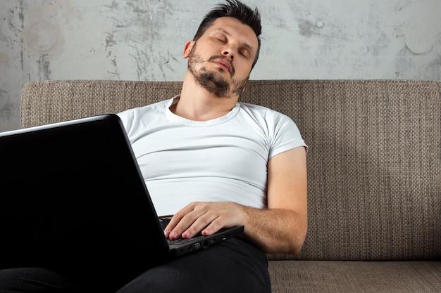 Mann trägt ein weißes hemd auf der couch sitzen, schlief bei der arbeit auf einem laptop.