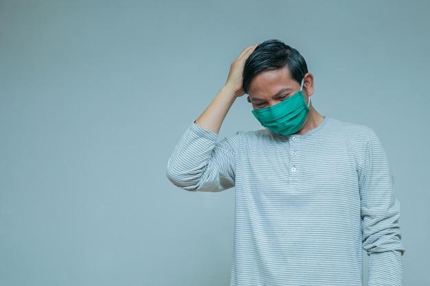 Mann trägt eine maske mit kopfschmerzen