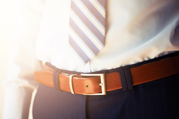 Mann trägt einen gürtel. junger geschäftsmann in der zufälligen klage mit zubehör. mode- und bekleidungskonzept. bräutigam, der morgens vor zeremonie fertig wird