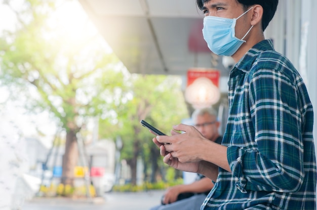 Mann trägt gesichtsmaske mit mobilem smartphone
