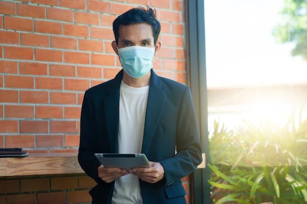 Mann trägt gesichtsmaske mit tablet-technologie
