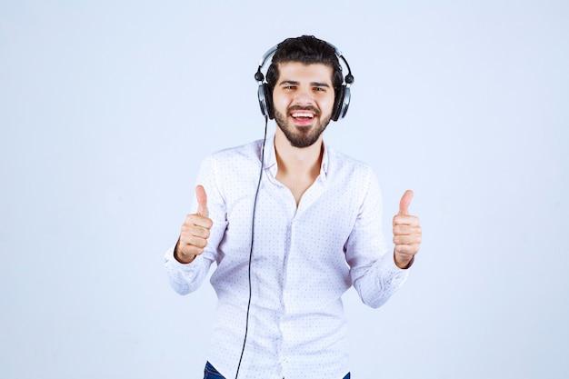 Mann trägt kopfhörer und genießt die musik