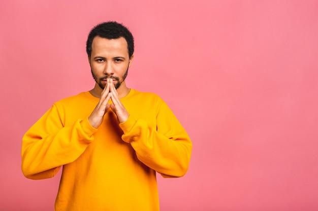 Mann trägt lässig stehend über isoliertem rosa betteln und beten mit händen zusammen mit hoffnungsausdruck auf gesicht sehr emotional und besorgt.