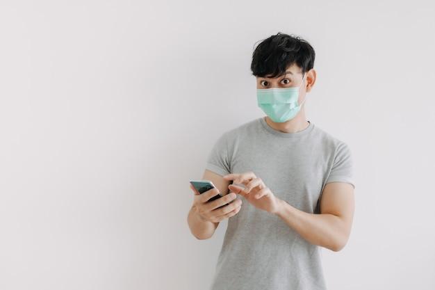 Mann trägt maske und verwendet telefonanwendung isoliert auf weißem hintergrund