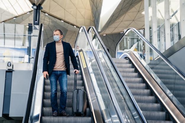 Mann trägt medizinische gesichtsmaske, posiert auf rolltreppe am flughafen, kommt aus dem ausland