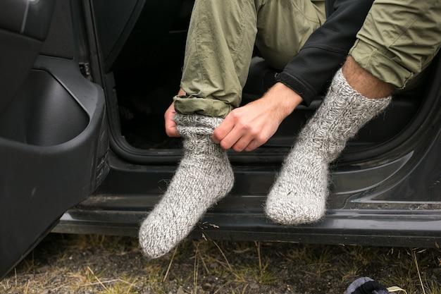 Mann trägt neue frische trockene socken nach der wanderung