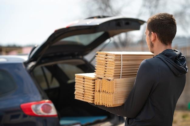 Mann trägt parkett zum auto baumaterialien für die reparatur und dekoration von räumlichkeiten holzmaterial