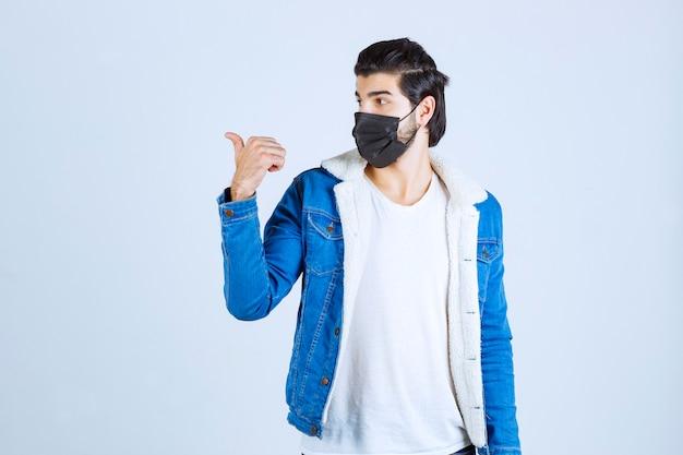 Mann trägt schwarze maske und zeigt nach links.