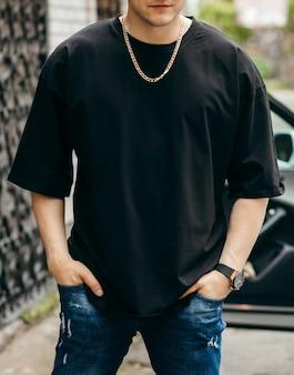 Mann trägt schwarzes leeres t-shirt mit platz für ihr logo oder design mock-up