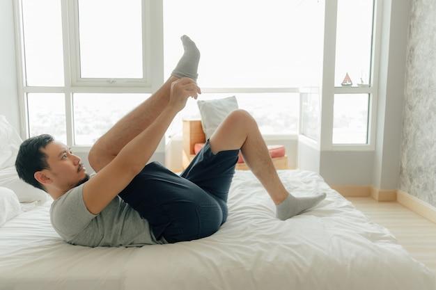 Mann trägt socken in seinen füßen im schlafzimmer.