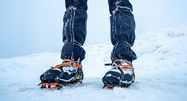 Mann trägt steigeisen auf trekkingschuhen im schnee