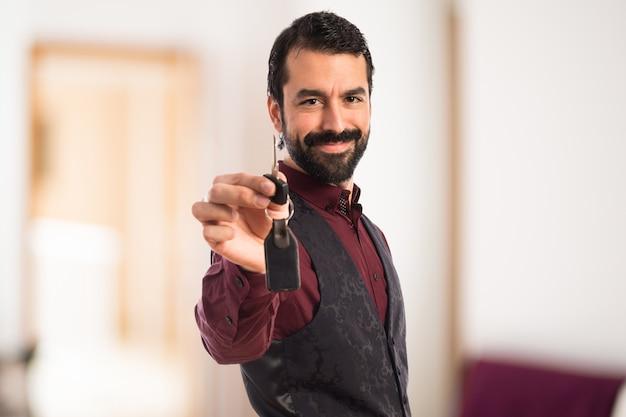 Mann trägt weste mit autoschlüssel auf unfocused hintergrund