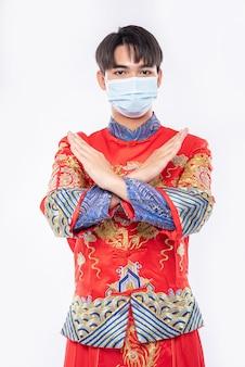 Mann tragen cheongsam anzug und maske zeigen menschen, die keine maske tragen, können nicht kommen, um im chinesischen neujahr einzukaufen