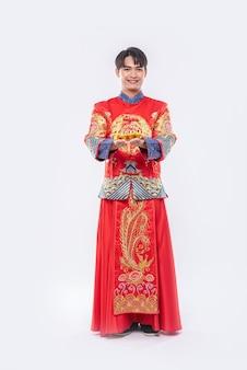 Mann tragen cheongsam anzug und schwarzen schuh geben seinem verwandten gold für glück im chinesischen neujahr
