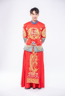 Mann tragen cheongsam lächeln, um reisende zu begrüßen, die im chinesischen neuen jahr einkaufen