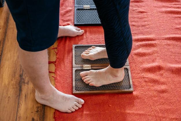 Mann trainer hilft frau, auf sadhu yoga board, barfuß auf einem bett von nägeln zu stehen