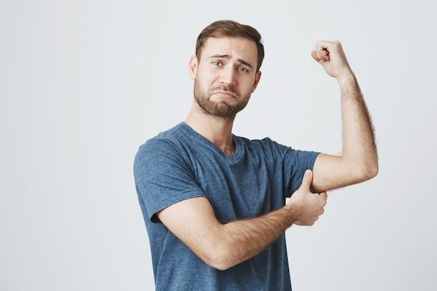 Mann trainieren fitnessstudio, zeigen starken bizeps