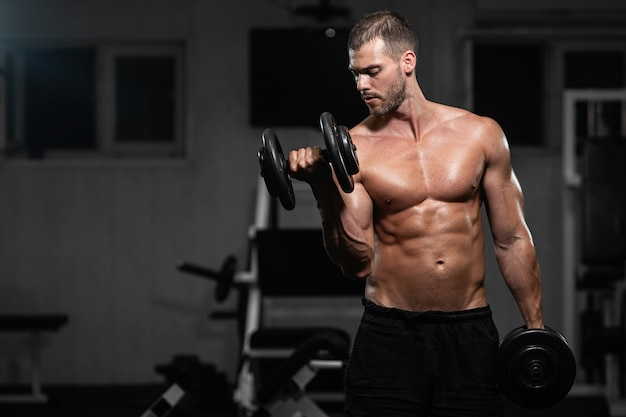 Mann trainiert im fitnessstudio. athletischer mann trainiert mit hanteln und pumpt seinen bizeps