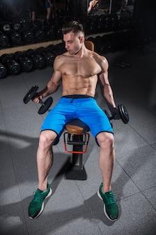 Mann trainiert in der turnhalle, fitness und bauchpresse
