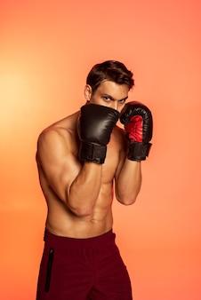 Mann trainiert mit boxhandschuhen mittlerer schuss