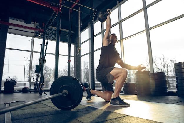 Mann trainiert mit hanteln im fitnessstudio