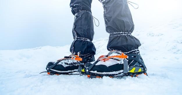 Mann trekking verschneiten berg mit steigeisen für tiefschnee