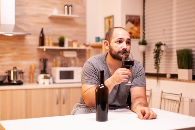 Mann trinkt allein zu hause wegen einsamkeit und traurigkeit. unglückliche krankheit und angst, die sich mit alkoholismusproblemen erschöpft fühlen.