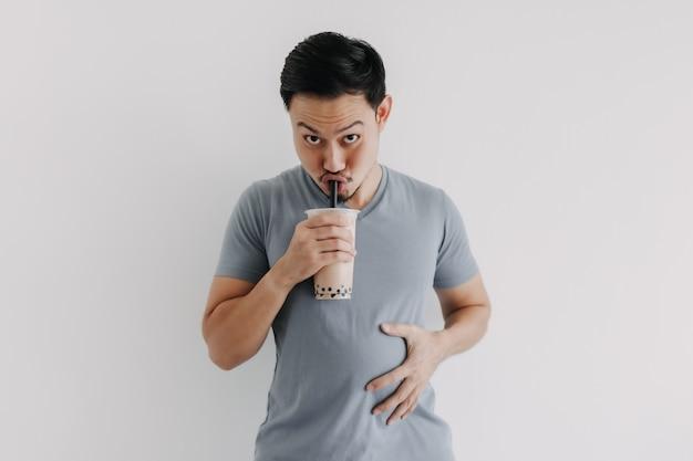 Mann trinkt boba-tee oder bubble tea köstlich isoliert auf weißem hintergrund