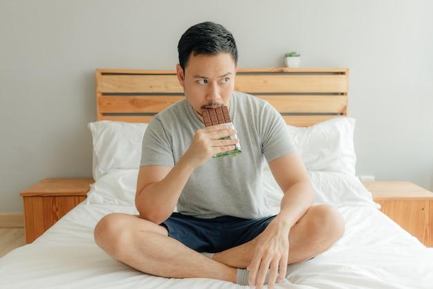 Mann trinkt eine tasse kaffee auf dem bett in seinem schlafzimmer.