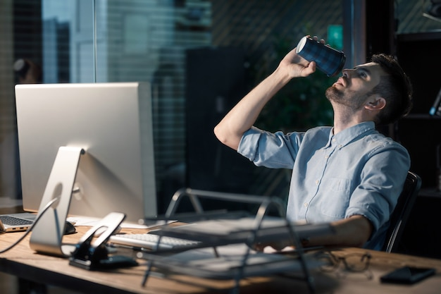 Mann trinkt kaffee, der stunden arbeitet