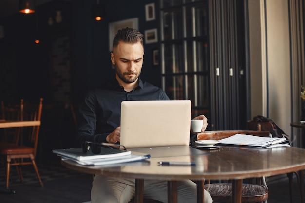 Mann trinkt kaffee. geschäftsmann liest dokumente. regisseur in einem hemd.