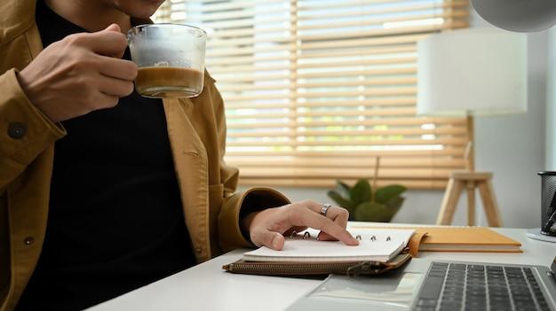 Mann trinkt kaffee und liest morgens ein buch.