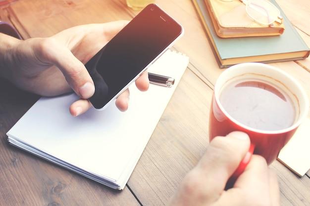 Mann trinkt kaffee und schaut auf den telefonbildschirm