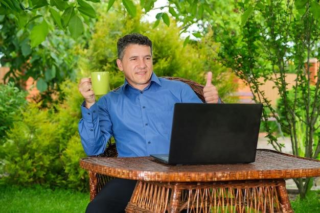 Mann trinkt kaffee und zeigt dem geschäftspartner über laptop den daumen thumb