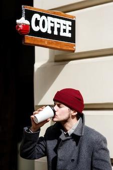 Mann trinkt kaffee unter dem schild mit schriftzug
