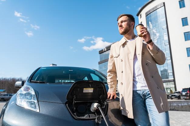 Mann trinkt kaffee, während er sein elektroauto auflädt