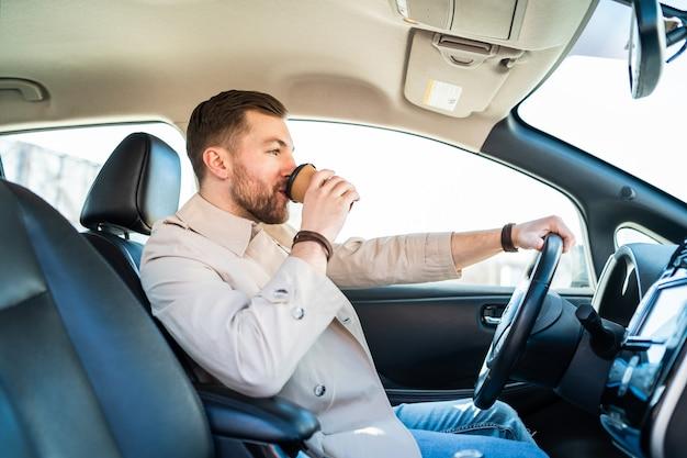 Mann trinkt morgenkaffee beim autofahren