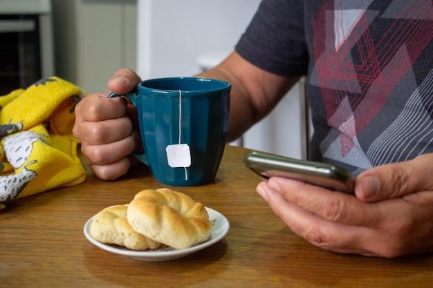 Mann trinkt tee und isst kekse mit blick auf sein telefon selektiver fokus