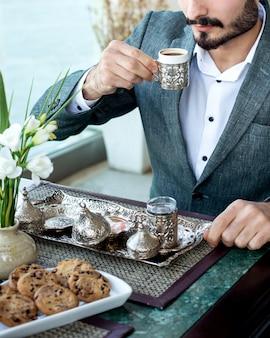 Mann trinkt türkischen kaffee mit lokum