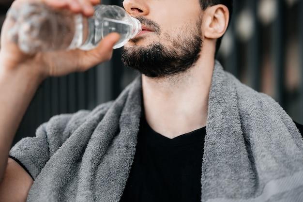 Mann trinkt wasser aus plastikflasche nach hartem training. nahaufnahme des männlichen gesichts. vergiss nicht, während des trainings zu trinken. achten sie auf sich selbst konzept. trinke mehr wasser. hydratation zeit!